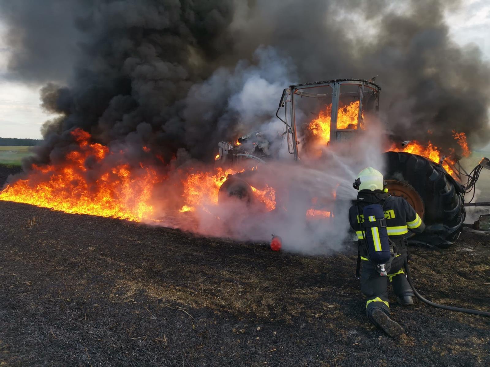 6_JČK_Požár traktoru_hořící stroj, před ním je zasahující hasič.jpg