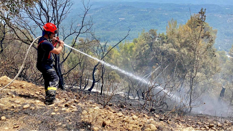 10_GŘ_pomoc při hašení požáru v Řecku_pohled na hořící krajinu a zasahujícího hasiče.jpg
